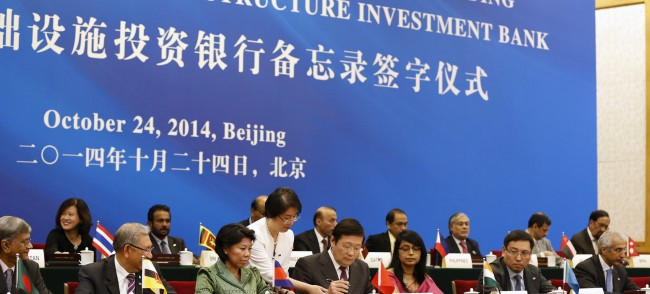 China's Finance Minister Lou Jiwei signs a document, with the guests of the signing ceremony of the Asian Infrastructure Investment Bank at the Great Hall of the People in Beijing